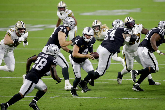 Las Vegas Raiders quarterback Derek Carr (4) prepares to hand the ball off to running back Josh Jacobs (28) during the first half of an NFL football game, Monday, Sept. 21, 2020, in Las Vegas. (AP Photo/Isaac Brekken)