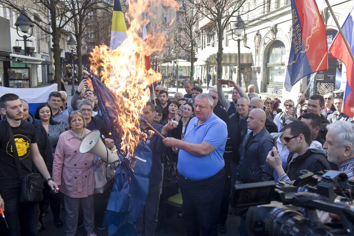 Vojislav Seselj, center, the leader of the ultranationalist Serbian Radical Party, holds a burning NATO flag as he and others gather for a protest in Belgrade, Serbia, Sunday, March 24, 2019. Members of the ultranationalist Serbian Radical Party gathered for a protest on Sunday in the Serbian capital to mark the 20th anniversary of the NATO led bombing campaign against Serbia in 1999. (AP Photo/Marko Drobnjakovic)