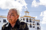 Leo Tudela recalls his allegations of sexual abuse at age 13 by a monk at the Saint Fidelis Friary, seen in the background, in Hagatna, Guam, Thursday, May 9, 2019. Tudela was eventually moved to live in the rectory of another church where Father Louis Brouillard took interest in him. That began an eight-month period during which Tudela alleges he was regularly raped and molested.