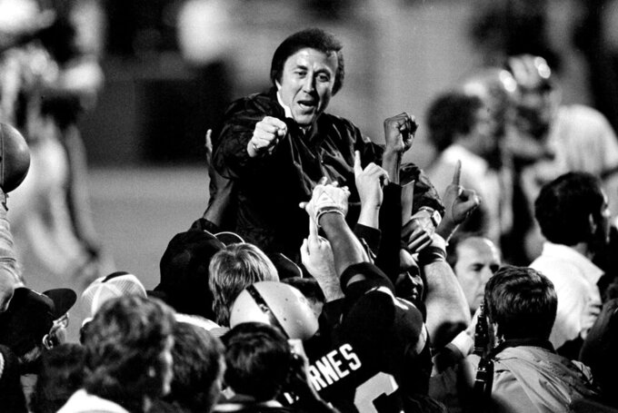 FILE - In this Jan. 23, 1984, file photo, coach Tom Flores gestures to members of the Los Angeles Raiders as they carry him off the field after their 38-9 victory over the Washington Redskins in Super Bowl XVIII in Tampa, Fla.  Flores has been selected as the Coach Finalist for the Pro Football Hall of Fame's Class of 2021. (AP Photo/File)