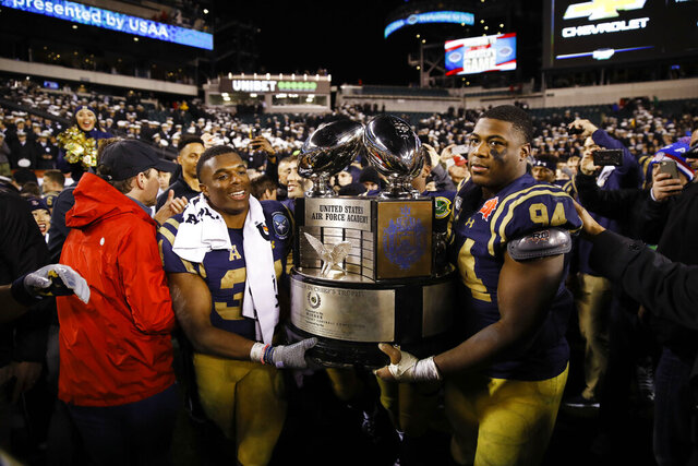 FILE - In this Saturday, Dec. 14, 2019, file photo, Navy midshipmen carry the Commander in Chief's trophy after defeating Army in an NCAA college football game, in Philadelphia. Navy won 31-7. After weeks and weeks of practice, Air Force will finally take the field Saturday, Oct. 3, 2020, against Navy at Falcon Stadium. The two service academies renew their rivalry as they compete for the coveted Commander-in-Chief's Trophy. (AP Photo/Matt Rourke, File)