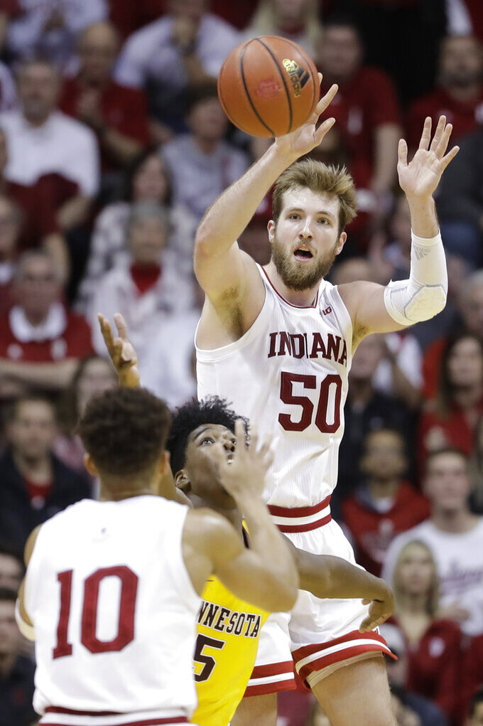 Indiana's Joey Brunk (50) passes the ball to Rob Phinisee (10) while being defended by Minnesota's Marcus Carr (5) during the second half of an NCAA college basketball game, Wednesday, March 4, 2020, in Bloomington, Ind. Indiana defeated Minnesota 72-67. (AP Photo/Darron Cummings)