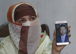 In this May 22, 2019 photo, Sumaira a Pakistani woman, shows a picture of her Chinese husband in Gujranwala, Pakistan. Sumaira, who didn't want her full name used, was raped repeatedly by Chinese men at a house in Islamabad where she was brought to stay after her brothers arranged her marriage to an older Chinese man. Her father had died when she was young, her mother was poor and her brothers were offered money to marry her to a Chinese businessman. (AP Photo/K.M. Chaudary)