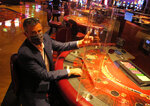 Ron Baumann, a regional president with Caesars Entertainment, sits Wednesday, July 1, 2020, at a card table at Harrah's casino in Atlantic City, N.J., where plexiglass barriers have been installed to separate gamblers to prevent the spread of the coronavirus. Five of Atlantic City's casinos will reopen on Thursday, while three others, including Harrah's, will open Friday. (AP Photo/Wayne Parry)