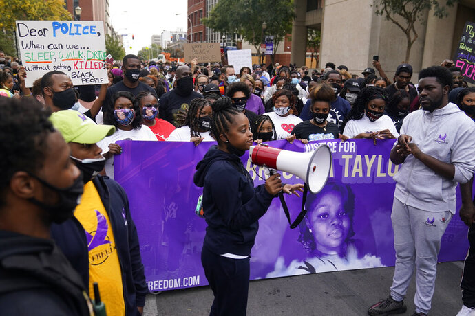 A woman speaks to gathered protesters, Friday, Sept. 25, 2020, in Louisville. Breonna Taylor's family demanded Friday that Kentucky authorities release all body camera footage, police files and the transcripts of the grand jury hearings that led to no charges against police officers who killed the Black woman during a March drug raid at her apartment. (AP Photo/Darron Cummings)