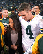 FILE - In this Dec. 22, 2003, file photo, Green Bay Packers quarterback Brett Favre is escorted off the field with his wife, Deanna, after the Packers defeated the Oakland Raiders 41-7 in an NFL football game in Oakland, Calif. When it comes to emotional games, his four-touchdown against the Raiders the day after his father's death in 2003 stands out above all the rest.  (AP Photo/Paul Sakuma, File)