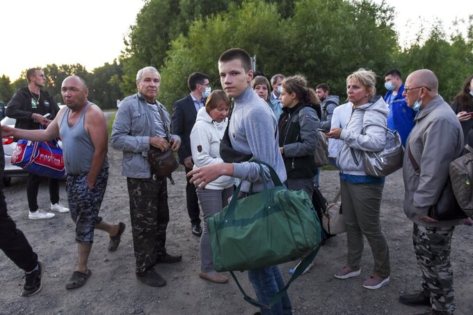 Passengers of An-28 plane, which made an emergency landing, and their relatives greet each other upon their landing in a rescue helicopter at an airport outside in Tomsk, Russia, Friday, July 16, 2021. Emergency officials say a small Russian passenger plane has made an emergency landing in Siberia after an engine failure. None of the 18 passengers and crew members suffered serious injuries. The An-28 plane went missing Friday in the Tomsk region in western Siberia. (Taisya Vorontsova/RIA Tomsk via AP)