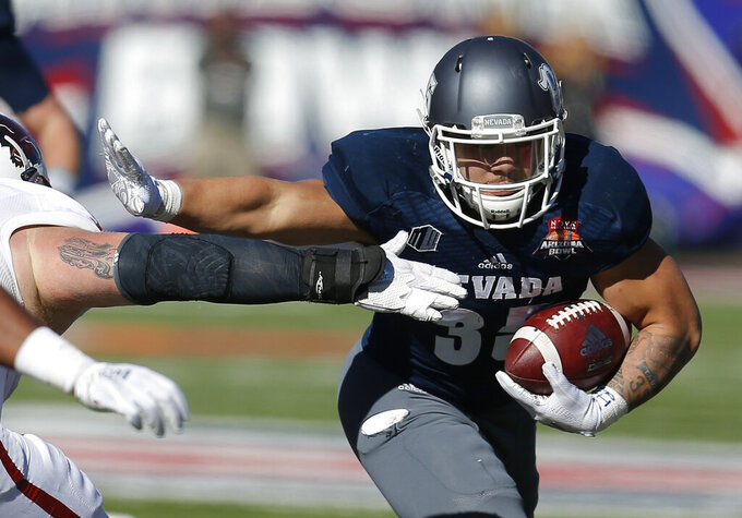 FILE - In this Dec. 29, 2018, file photo, Nevada running back Toa Taua (35) carries during the first half of the Arizona Bowl NCAA college football bowl game against Arkansas State in Tucson, Ariz. Nevada sophomore running back Taua rushed for 872 yards and six TDs last year for Nevada. Coming off breakout freshman seasons, Purdue wide receiver Rondale Moore and Nevada's Taua headline Friday night's non-conference opener on the edge of the Sierra where both third-year coaches hope to turn the corner on rebuilding efforts. (AP Photo/Rick Scuteri, File)
