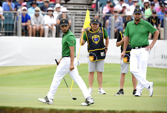 International team player Abraham Ancer of Mexico, left, and playing partner Marc Leishman of Australia, right, survey the 16th green in their foursomes match during the President's Cup golf tournament at Royal Melbourne Golf Club in Melbourne, Friday, Dec. 13, 2019. (AP Photo/Andy Brownbill)