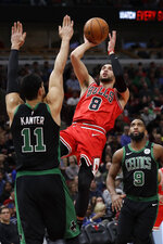 Chicago Bulls guard Zach LaVine (8) shoots over Boston Celtics center Enes Kanter (11) as guard Brad Wanamaker (9) watches during the first half of an NBA basketball game in Chicago, Saturday, Jan. 4, 2020. (AP Photo/Nam Y. Huh)