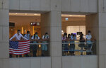 Protesters displays a U.S. flag in a shopping mall during a protest against China's national security legislation for the city, in Hong Kong, Monday, June 1, 2020. The mouthpiece of China's ruling Communist Party says U.S. moves to end some trading privileges extended to Hong Kong grossly interfere in China's internal affairs and are doomed to fail. (AP Photo/Vincent Yu)