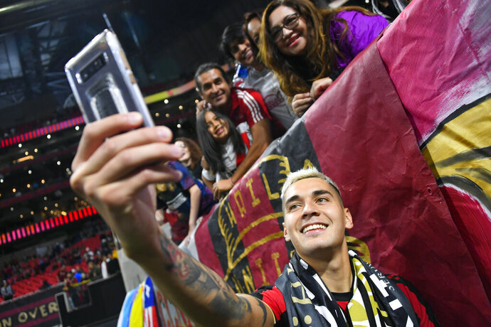 Atlanta United defender Franco Escobar takes a selfie with fans after round one of an MLS Cup playoff soccer game against the New England Revolution, Saturday, Oct. 19, 2019, in Atlanta. Atlanta won 1-0. (AP Photo/John Amis)