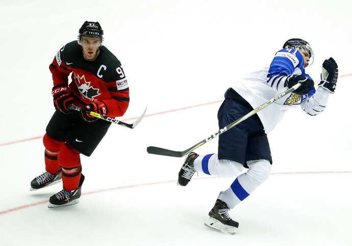 Canada's Connor McDavid, left, fouls Finland's Miro Heiskanen, right, during the Ice Hockey World Championships group B match between Canada and Finland at the Jyske Bank Boxen arena in Herning, Denmark, Saturday, May 12, 2018. (AP Photo/Petr David Josek)