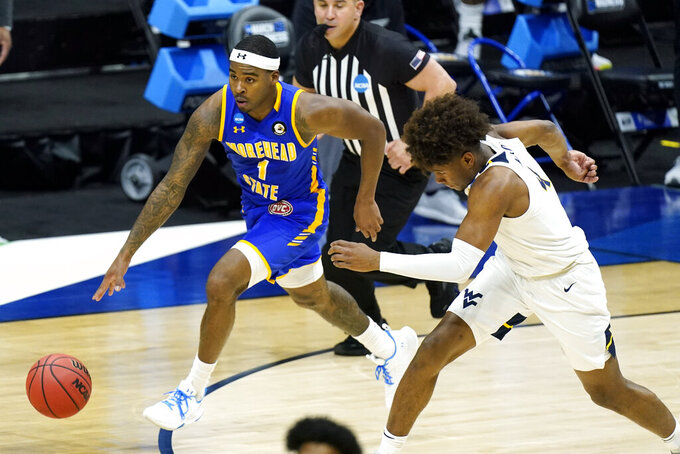 Morehead State's DeVon Cooper (1) brings the ball up the court against West Virginia during the first half of a college basketball game in the first round of the NCAA tournament at Lucas Oil Stadium Friday, March 19, 2021, in Indianapolis. (AP Photo/Mark Humphrey)