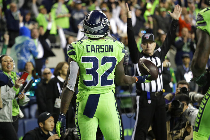 Seattle Seahawks running back Chris Carson holds the ball after scoring a touchdown against the Los Angeles Rams during the second half of an NFL football game Thursday, Oct. 3, 2019, in Seattle. (AP Photo/Elaine Thompson)