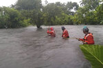 In this photo provided by the Philippine Coast Guard, members of the Philippine coastguard wade along floodwaters as the look for residents to be evacuated to safer grounds, in Naujan, Oriental Mindoro province, central Philippines on Friday July 23, 2021. Thousands of residents fled from flooded communities and swollen rivers in the Philippine capital and outlying provinces Saturday after days of torrential monsoon rains, which left at least one villager dead, officials said. (Philippine Coast Guard via AP)