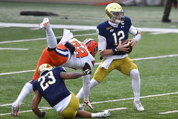 Syracuse cornerback Kyle Strickland (22) pressures Notre Dame quarterback Ian Book (12) in the first half of an NCAA college football game Saturday, Dec. 5, 2020, in South Bend, Ind. (Matt Cashore/Pool Photo via AP)