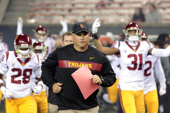 FILE - In this Nov. 3, 2018, file photo, Southern California head coach Clay Helton leads his team onto the field before an NCAA college football game in Corvallis, Ore. Helton has told his players not to worry about his job security as they head into the final two games of their 5-5 regular season. Helton realizes fans are unhappy just one season after he led the Trojans to the Pac-12 title.  (AP Photo/Timothy J. Gonzalez, File)