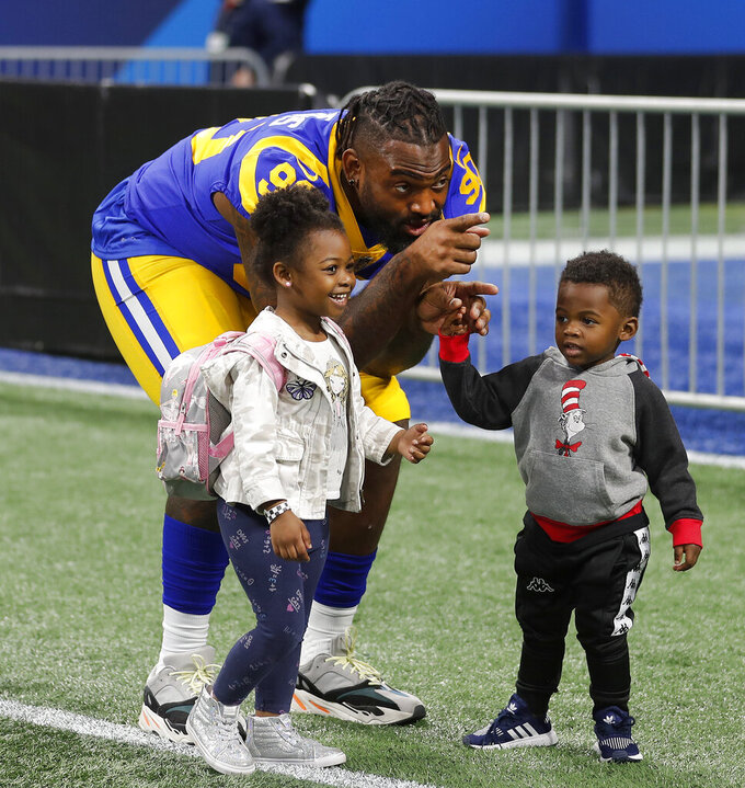 Los Angeles Rams defensive end Michael Brockers (90) plays with his children during walkthrough at the Mercedes Benz Stadium for the NFL Super Bowl 53 football game against the New England Patriots, Saturday, Feb. 2, 2019, in Atlanta. (AP Photo/John Bazemore)