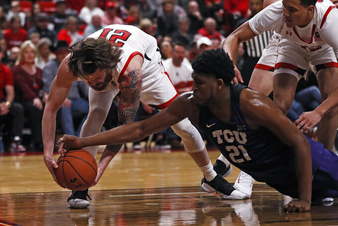 Texas Tech's Avery Benson (21) and TCU's Kevin Samuel (21) grab for the ball during the second half of an NCAA college basketball game Monday, Feb. 10, 2020, in Lubbock, Texas. (AP Photo/Brad Tollefson)