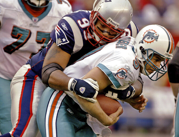 FILE - In this Oct. 10, 2004, file photo, Miami Dolphins quarterback Jay Fiedler (9) is sacked by New England Patriots defensive lineman Richard Seymour (93) during first-quarter action of their AFC East conference game Sunday afternoon Oct. 10, 2004 in Foxborough, Mass. Chosen sixth overall in the NFL draft in 2001, Seymour is the highest selection ever made by Bill Belichick during his Patriots tenure. A member of New England's first three Super Bowl-winning teams in the 2001, 2003 and 2004 seasons, Seymour was one of the most destructive forces on the defensive side of the ball for those teams. (AP Photo/Stephan Savoia, File)