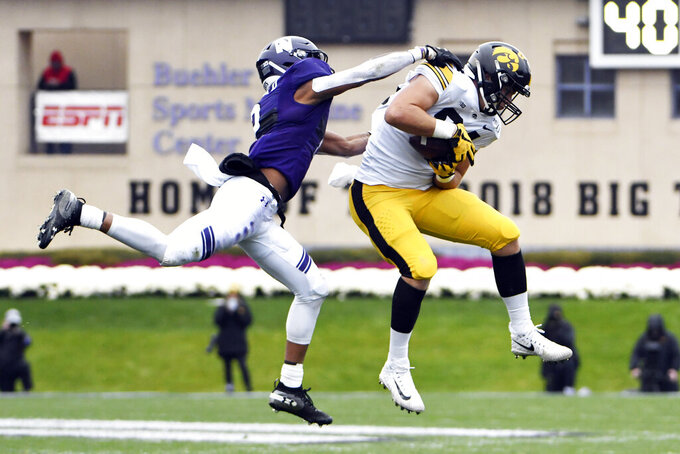 Iowa tight end Sam LaPorta, right, catches a pass as Northwestern defensive back Greg Newsome II, left, defends him during the first half of an NCAA college football game, Saturday, Oct. 26, 2019, in Evanston, Ill. (AP Photo/David Banks)