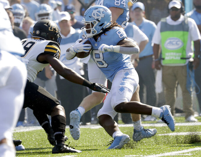 North Carolina's Michael Carter (8) evades a tackle by Appalachian State's Brendan Harrington (29) as he runs the opening kickoff for a big gain during the first quarter of an NCAA college football game in Chapel Hill, N.C., Saturday, Sept. 21, 2019. (AP Photo/Chris Seward)