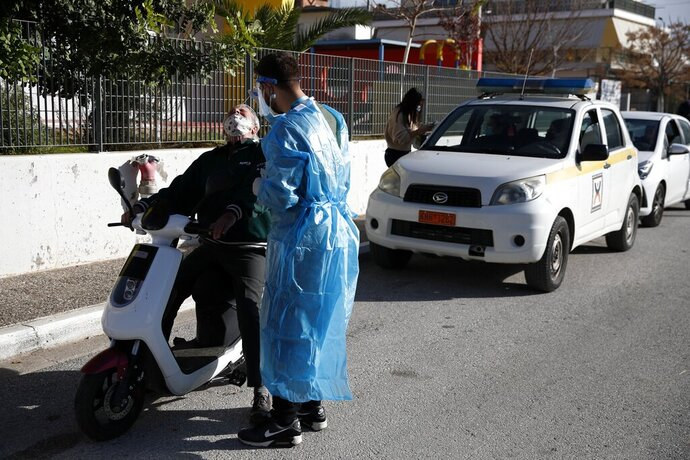 A medical staff member of the National Health Organization (EODY) conducts a COVID-19 rapid test on a man at a drive-through testing site at Aspropyrgos suburb, west of Athens, Friday, Jan. 8, 2021. The western municipality of the Greek capital remains in a hard lockdown due to their heavy epidemiological burden as Greece will ramp up the speed of its coronavirus vaccination drive, the country's prime minister said Friday. (AP Photo/Thanassis Stavrakis)