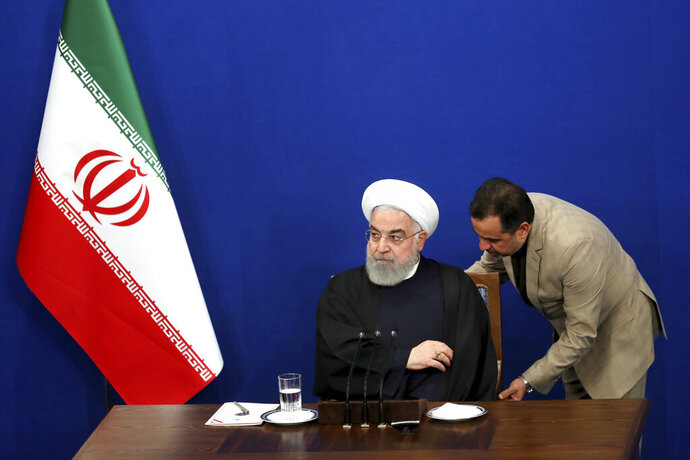 An unidentified presidency staff at right adjusts the seat for Iranian President Hassan Rouhani while he arrives for his press conference in Tehran, Iran, Sunday, Feb. 16, 2020. Rouhani said Sunday  that he doesn't believe the U.S. will pursue war with his country, because it will harm President Donald Trump's 2020 reelection bid. Tensions have been escalating steadily since Trump pulled the U.S. out of Tehran's 2015 nuclear deal with world powers, and reimposed crippling sanctions on Iran. (AP Photo/Ebrahim Noroozi)