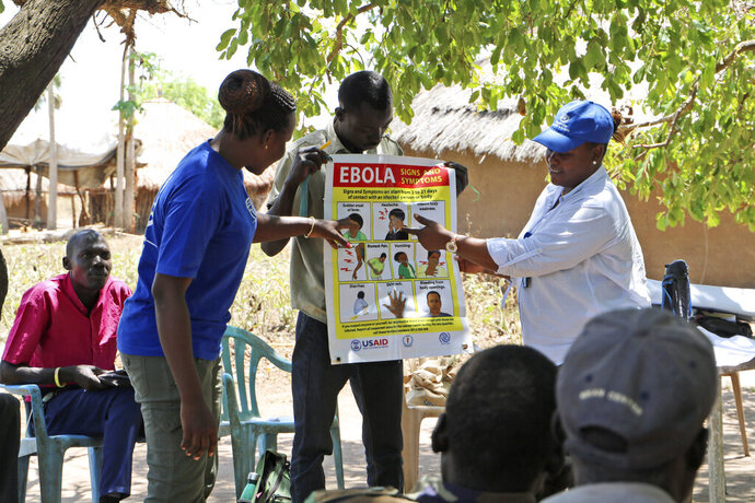 In this Tuesday Feb. 26 2019 photo, health workers give a training presentation about how to detect and prevent the spread of Ebola, in an army barracks outside South Sudan's town of Yei. With the deadly Ebola outbreak in Congo now an international emergency, neighboring South Sudan and its war-weakened health system is a major concern, especially after one case was confirmed near its border. Health experts say there is an urgent need to increase prevention efforts. (AP Photo/ Sam Medrick)
