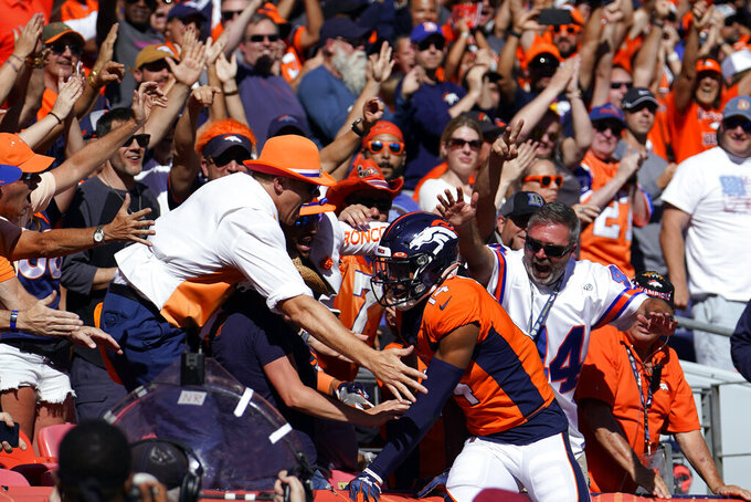 Denver Broncos wide receiver Courtland Sutton, below right, reacts with fans after scoring a touchdown during the first half of an NFL football game against the Jacksonville Jaguars, Sunday, Sept. 29, 2019, in Denver. (AP Photo/Jack Dempsey)