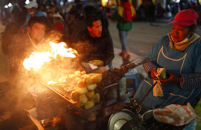 A street vendor keeps food warm on the sidelines of a gathering of people against the reelection of President Evo Morales, in La Paz, Bolivia, Thursday, Oct. 31, 2019. Violence has escalated since Morales was declared the winner of the Oct. 20 vote amid delays in the vote count. The opposition alleges the outcome was rigged to give Morales enough of a majority to avoid a runoff election; the president denies any irregularities. (AP Photo/Juan Karita)