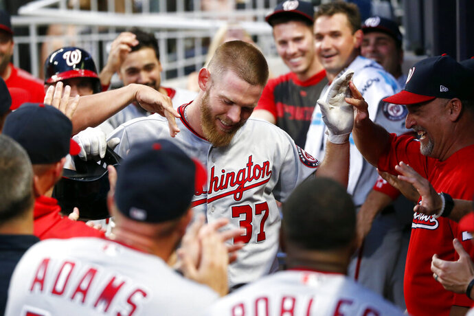 Washington Nationals starting pitcher Stephen Strasburg (37) is congratulated in the dugout after hitting a two-run home run during the third inning of the team's baseball game against the Atlanta Braves on Thursday, July 18, 2019, in Atlanta. (AP Photo/John Bazemore)
