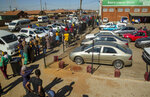 Customers queue to purchase alcoholic beverages outside the Sam Liquor Store in Thokoza township, near Johannesburg, South Africa, Monday, June 1, 2020.  Liquor stores have reopened Monday after being closed for over two months under lockdown restrictions in a bid to prevent the spread of coronavirus. (AP Photo/Themba Hadebe)