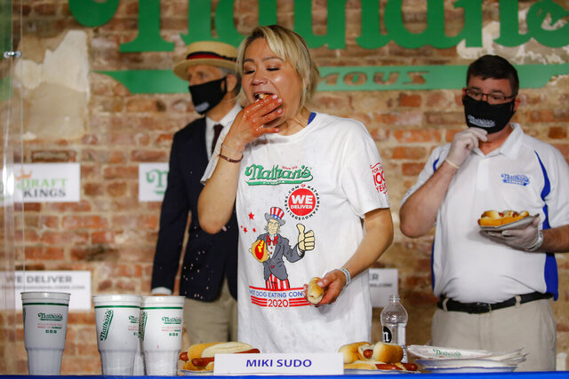 Competitive eater Miki Sudo eats a record 48 and a half hot dogs to win the women's division of the Nathan's Famous July Fourth hot dog eating contest, Saturday, July 4, 2020, in the Brooklyn borough of New York. (AP Photo/John Minchillo)