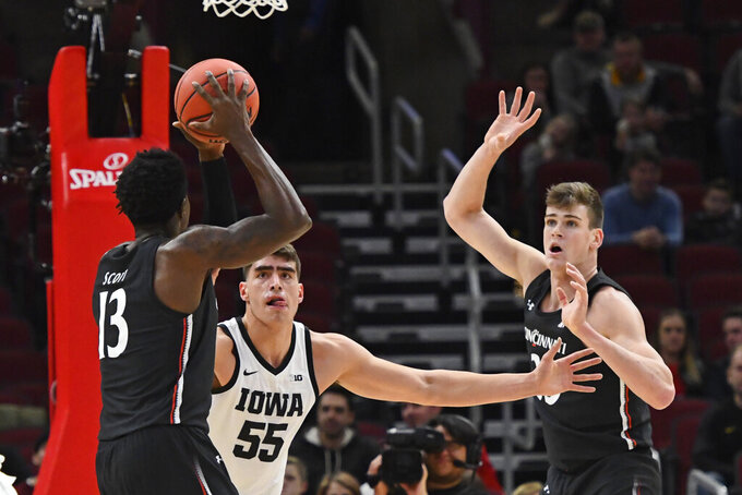 Cincinnati forward Tre Scott (13) passes the ball to center Chris Vogt, right, as Iowa center Luka Garza (55) defends during the first half of an NCAA college basketball game Saturday, Dec. 21, 2019, in Chicago. (AP Photo/Matt Marton)