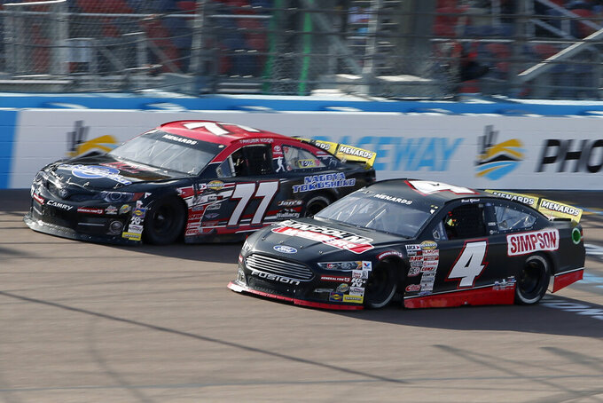 David Gilliland (4) and Takuma Koga (77), of Japan, race through Turn 4 during the ARCA Series auto race at Phoenix Raceway, Saturday, Nov. 7, 2020, in Avondale, Ariz. (AP Photo/Ralph Freso)