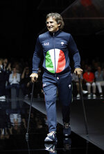 FILE -- In this photo taken on Saturday, June 15, 2019 file photo, Alex Zanardi takes the catwalk during the Emporio Armani men's Spring-Summer 2020 collection, unveiled during the fashion week, in Milan, Italy. Alex Zanardi, the Italian auto racing champion-turned-Paralympic gold medalist, was transferred to a neurological rehabilitation center Tuesday, July 21, 2020, a month after getting seriously injured in a handbike crash. The Siena hospital that had been treating Zanardi since the June 19 crash announced that the athlete had been released -- without specifying where he was taken. (AP Photo/Luca Bruno, File)
