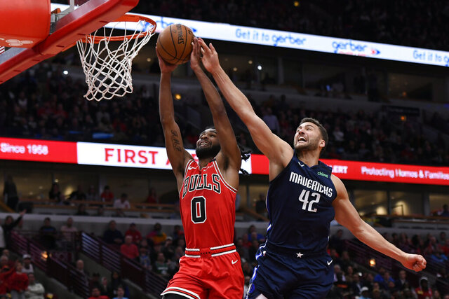 Chicago Bulls' Coby White (0) attempts to dunk against Dallas Mavericks' Maxi Kleber (42), of Germany, during the second half of an NBA basketball game Monday, March 2, 2020, in Chicago.  (AP Photo/Paul Beaty)