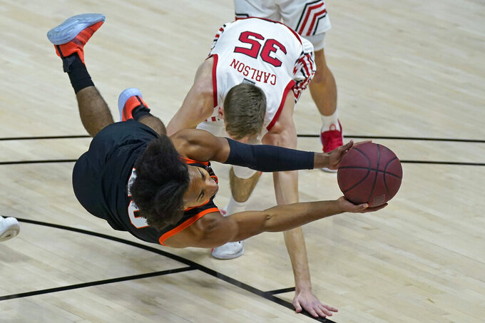 Idaho State guard Robert Ford III, foreground, tries to get a shot off against Utah Utes center Branden Carlson (35)during the first half of an NCAA college basketball game Tuesday, Dec. 8, 2020, in Salt Lake City. (AP Photo/Rick Bowmer)