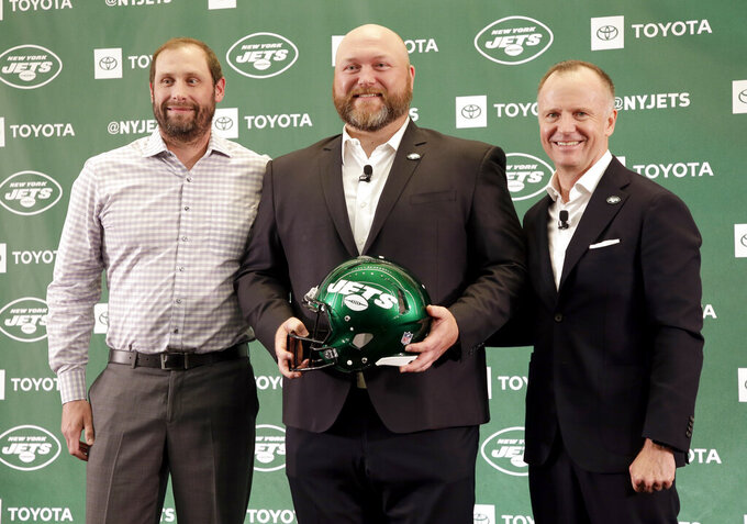 FILE - In this June 11, 2019, file photo, New New York Jets general manager Joe Douglas, center, poses for a picture with head coach Adam Gase, left, and Jets chairman and CEO Christopher Johnson during a news conference at the team's NFL football training facility in Florham Park, N.J. Johnson says Gase's job is safe and he will remain the coach next season despite the team's struggles this year. Johnson held a brief meeting with reporters and says Gase has his trust as well as the trust of general manager Joe Douglas moving forward. (AP Photo/Seth Wenig, File)