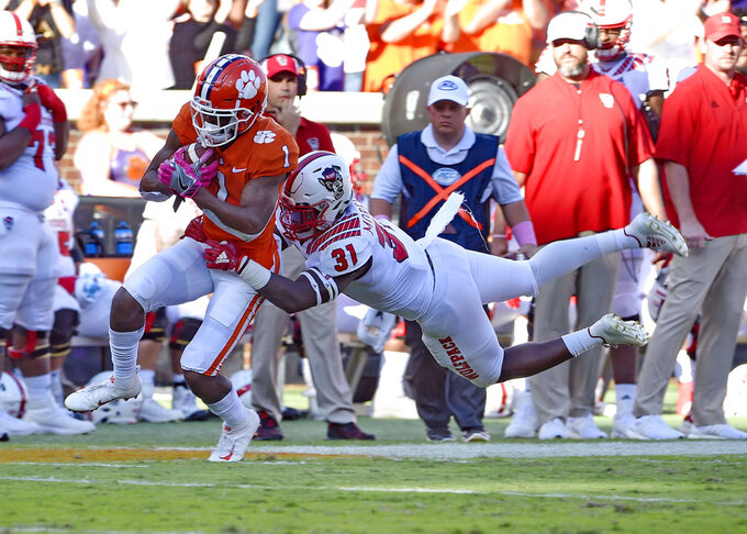 Clemson's Trevion Thompson rushes after a catch while defended by North Carolina State's Jarius Morehead during the first half of an NCAA college football game Saturday, Oct. 20, 2018, in Clemson, S.C. (AP Photo/Richard Shiro)