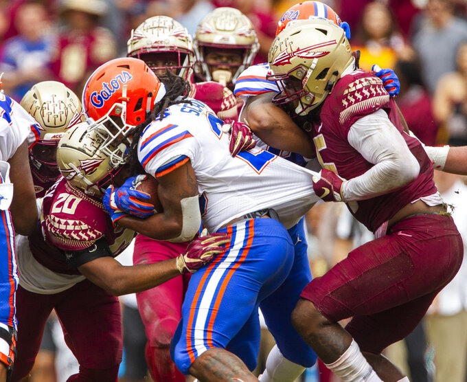Florida State defensive back Jaiden Woodbey (20) and linebacker Dontavious Jackson (5) stop Florida running back Jordan Scarlett (25) in the first half of an NCAA college football game in Tallahassee, Fla., Saturday, Nov. 24, 2018. (AP Photo/Mark Wallheiser)