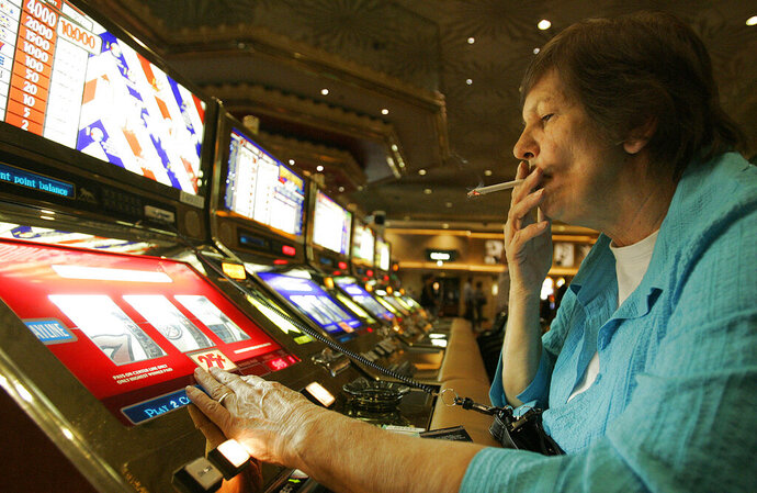 FILE - In this Dec. 28, 2005, file photo, Judy King of Daytona Beach, Fla., holds her cigarette while playing a slot machine at the MGM Grand hotel-casino in Las Vegas. One of the last Las Vegas Strip resorts to reopen after coronavirus closures will be the first to be smoke-free, MGM Resorts International announced Monday, Sept. 14, 2020. Park MGM will prohibit tobacco smoke inside when it opens Sept. 30, said Anton Nikodemus, president and chief operating officer of the 3,000-room property that many remember as the Monte Carlo casino-hotel. (AP Photo/Jae C. Hong, File)