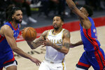 Dallas Mavericks guard Trey Burke, center, drives to the basket against Detroit Pistons center Jahlil Okafor (13) and guard Saben Lee (38) during the first half of an NBA basketball game Thursday, April 29, 2021, in Detroit. (AP Photo/Duane Burleson)