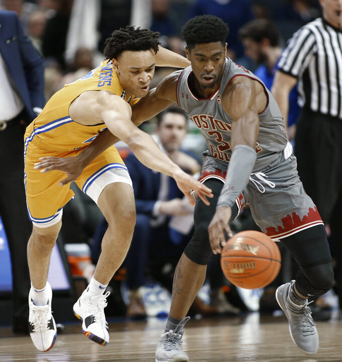 Pittsburgh's Trey McGowens, left, and Boston College's Jared Hamilton, right, chase the ball during the first half of an NCAA college basketball game in the Atlantic Coast Conference men's tournament in Charlotte, N.C., Tuesday, March 12, 2019. (AP Photo/Nell Redmond)