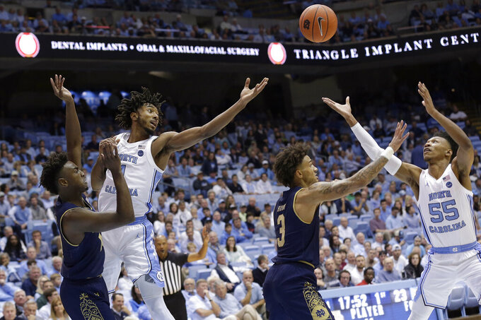 Notre Dame guard TJ Gibbs, left, and guard Prentiss Hubb (3) struggle for the ball with North Carolina guard Leaky Black, second from left, and guard Christian Keeling (55) during the first half of an NCAA college basketball game in Chapel Hill, N.C., Wednesday, Nov. 6, 2019. (AP Photo/Gerry Broome)
