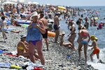 People enjoy the beach in the Black Sea resort of Sochi, Russia Sunday, July 5, 2020. Tens of thousands of vacation-goers in Russia and Ukraine have descended on Black Sea beaches, paying little attention to safety measures despite levels of contagion still remaining high in both countries. (AP Photo/Artur Lebedev)