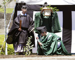 Shinto priests attend a ground-breaking ceremony at the Imperial Palace in Tokyo Friday, July 26, 2019. The ceremony was held in the compound of the palace, offering sake, rice and silk fabric to pray for safe and successful construction of a pair of shrines for Emperor Naruhito's key succession rituals later this year. (Kyodo News via AP)