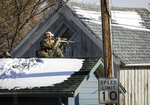 A sniper sits on a garage roof across the alley during a shots fired call at 812 5th Street that escalated to group of barricaded individuals on Tuesday, Nov. 12, 2019. Tactical officers responded to a home near downtown Rapid City after someone fired a gun from a car into a first-floor bedroom. Police say no one was hurt in Tuesday's shooting near Rapid City High School.  (Adam Fondren/Rapid City Journal via AP)